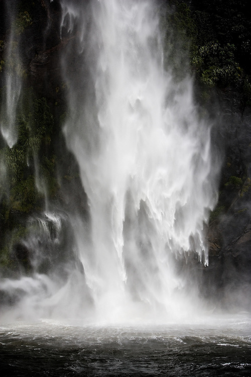 THE GUSHING WATERFALL IN THE MILFORD SOUND, NEW ZEALAND