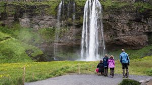Tourists at the base of the waterfall
